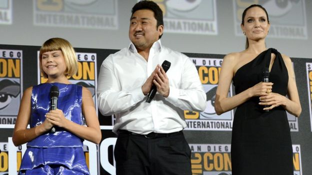 Lia McHugh, Dong-seok Ma and Angelina Jolie stand on stage