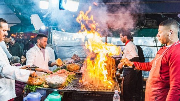 Men barbecue food as flames rise at a market stall in Marrakesh
