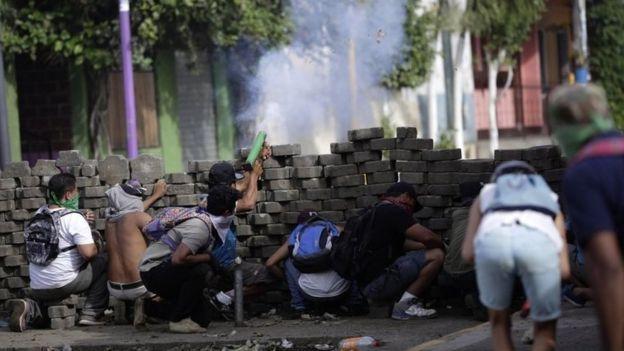 Manifestantes encapuzados atiram atrás de uma barricada