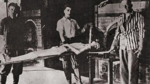 Três homens participam de encenação do processo de cremação; na imagem, é possível ver um aparente corpo e fornos