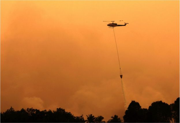 A helicopter drops water to extinguish a raging fire in Ogan Komering Ilir, South Sumatra Province, Indonesia, 13 September 2015