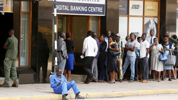 People queue to withdraw money outside a bank in Harare, Zimbabwe,
