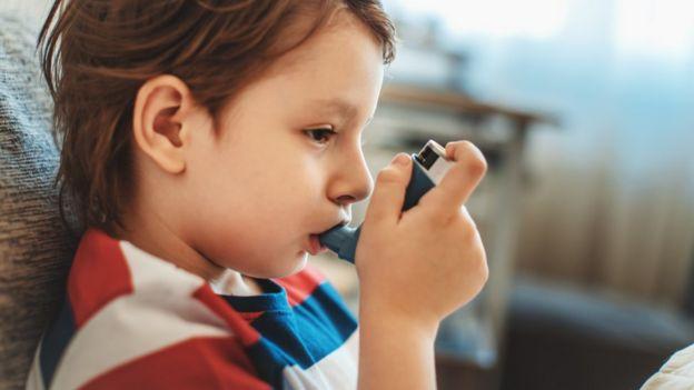 Un niño tomando un inhalador para el asma.