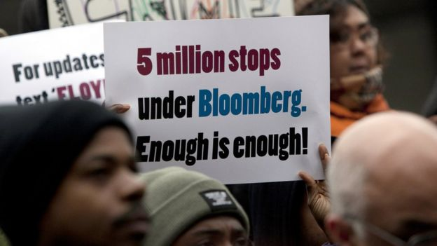 At a protest someone holds a sign that says five million stops under Bloomberg. Enough is enough!