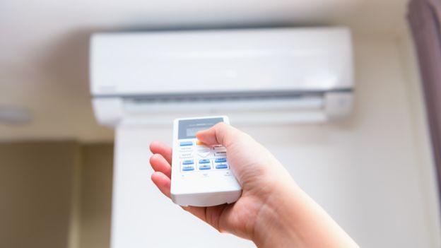 Una persona tiene en su mano el control remoto de un sistema de aire acondicionado
