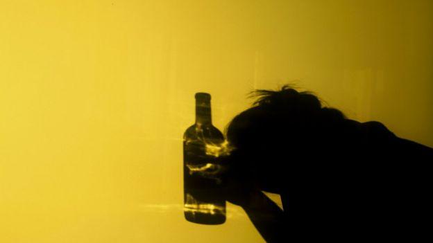 Vulto de mulher ao lado de uma garrafa de bebida