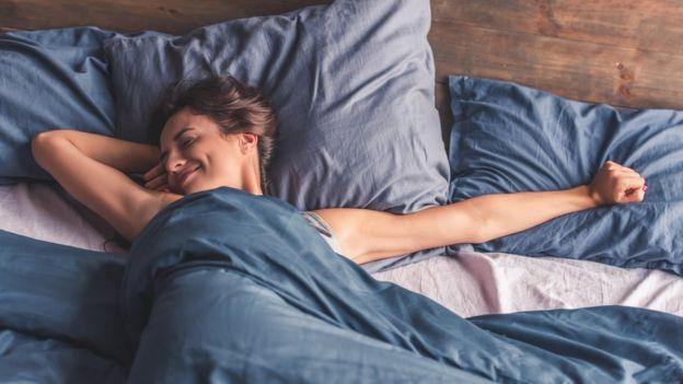 Девушка улыбается и потягивается в кровати