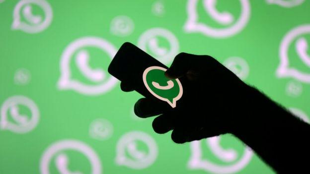 Homem segura celular cuja tela exibe logo do WhatsApp
