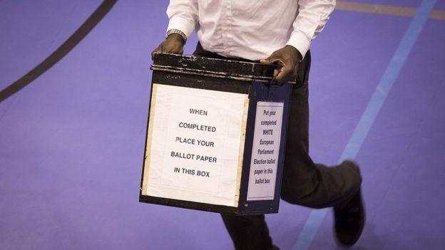 Кутия за гласуване, съдържаща гласове в европейските избори, пристига в училище Тринити на май 22, 2014 в Кройдън, Англия.