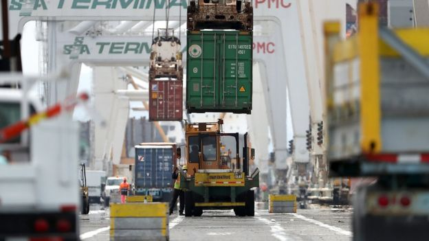 A shipping container is offloaded in a port in California