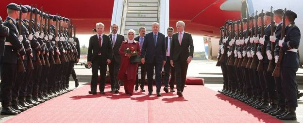 Mr Erdogan and his wife, along with senior officials, are accompanied down a red carpet flanked by a military honour guard.