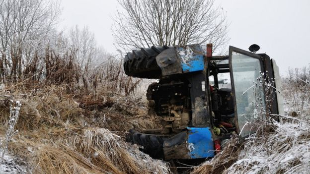 A tractor on its side in a ditch
