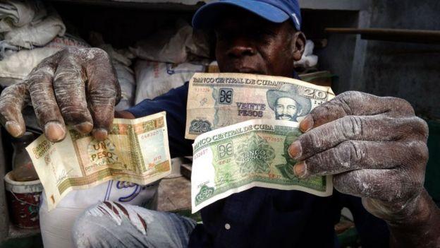 Un hombre muestra billetes de pesos convertibles y pesos cubanos.