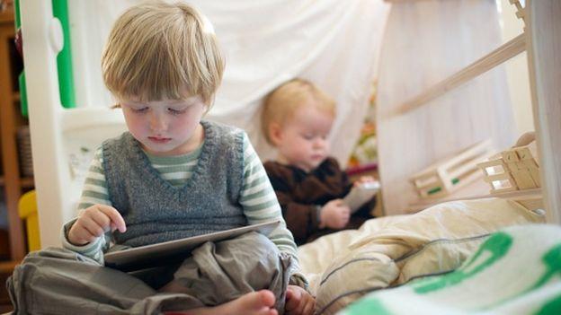 Un niño y un bebé miran sus pantallas