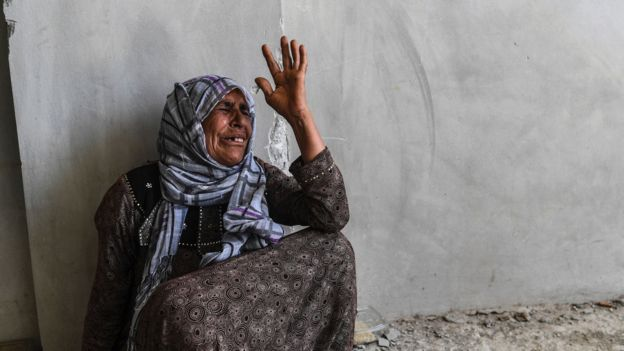 A member of the Sheikh Wais family reacts as she asks Kurdish fighters to recover the bodies of her relatives from under the rubble of a building in western Raqqa on 12 July 2017