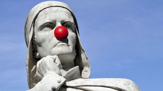 A marble statue. Close up of the stern face, wearing a clown red nose.