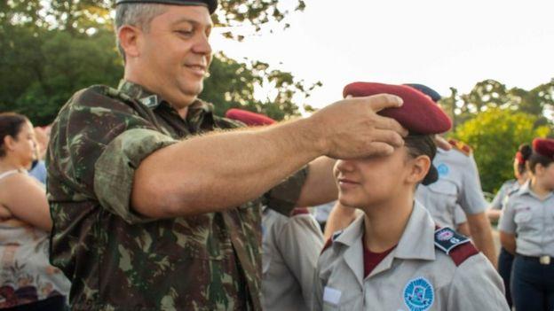 Militar colocando uma boina vermelha em uma aluna do colégio Vila Militar, de Curitiba