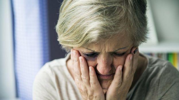 Una mujer se agarra la cara