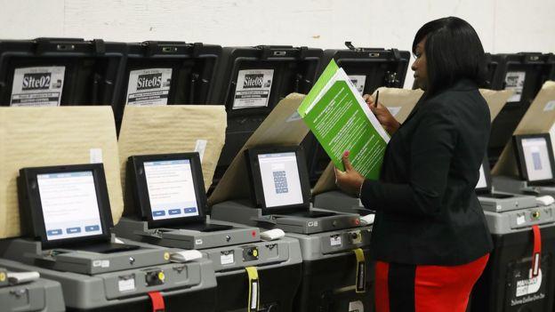 Mujer revisa máquinas de votación