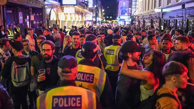 Police officers are seen walking through heavy crowds in Soho, central London