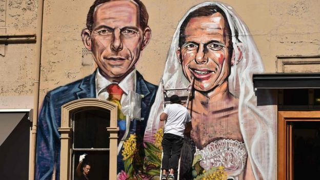 Australian street artist Scottie Marsh (C) painting a mural depicting former Australian prime minister Tony Abbott as the bride of Tony Abbott, in Sydney.