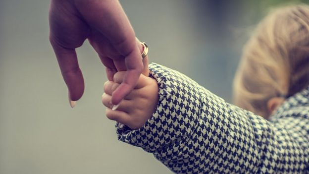 A woman's hand holding a child's hand