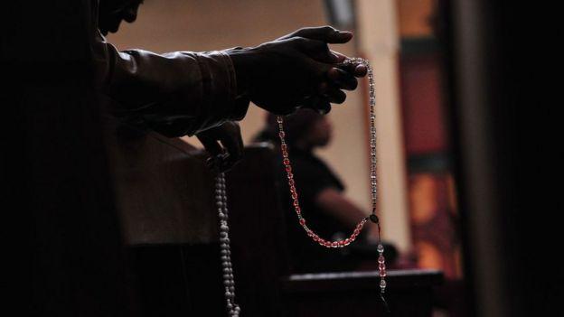Una persona con un rosario cristiano