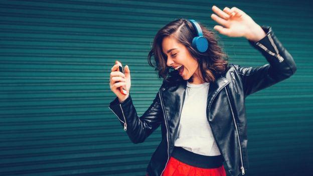 Garota feliz dançando com fone de ouvido