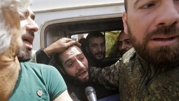 A vehicle transporting civilians and soldiers who the regime says were kidnapped by rebels and liberated in a prisoner swap arrives in a government-held area at the entrance of Harasta in Eastern Ghouta, on the outskirts of Damascus, on March 22, 2018