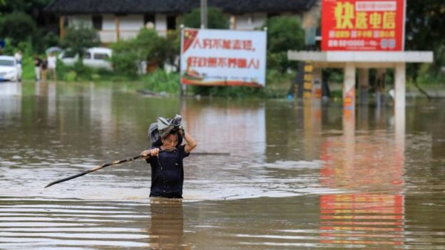 A man wades through floodwater in Rongan in China's southern Guangxi region