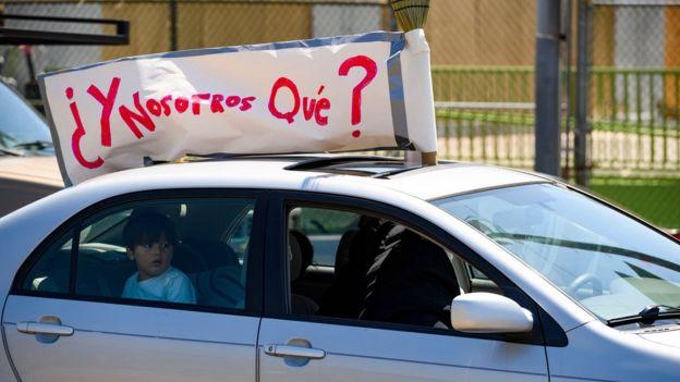 """Auto con un cartel que dice """"¿Y nosotros qué?"""""""