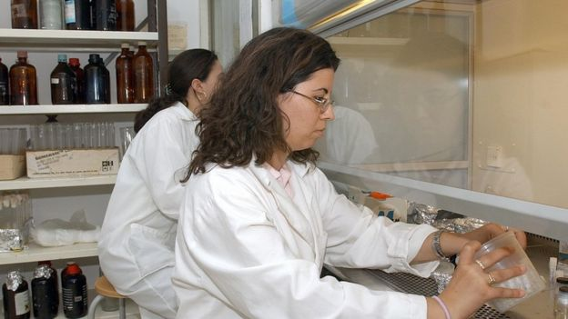 Two women handle chemicals behind a protective screen in a lab in Tunis.