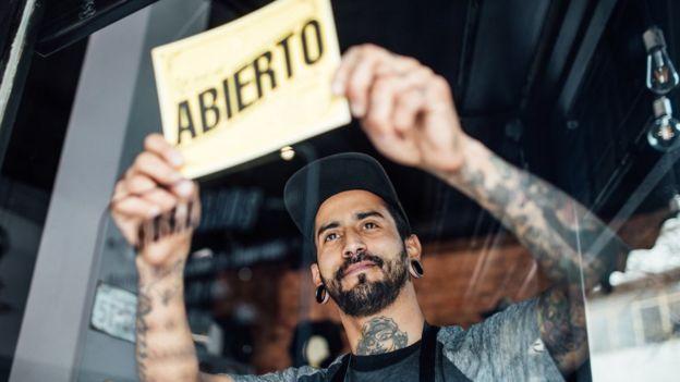 Joven latino abriendo colgando el cartel de abierto en un restaurante.