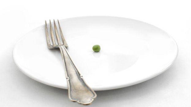 Un plato con una arveja y un tenedor