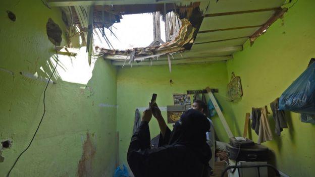 سيدة تصور سقف منزلها الذي أصابته بقايا صاروخ في حي أم الحمام في مدينة الرياض.