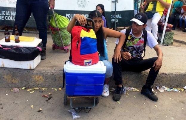Personas sentadas en el cruce fronterizo