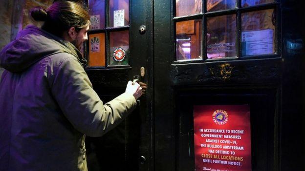 Un hombre entrando en un bar en el Barrio Rojo de Ámsterdam.