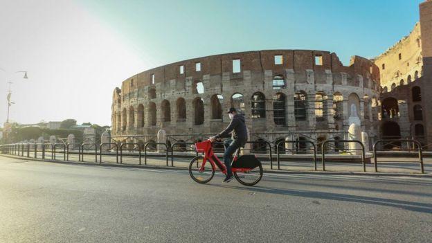Un hombre con mascarilla circula en bicicleta frente al Coliseo en Roma, Italia.
