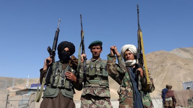 Taliban militants pose with an Afghan soldier during a three-day ceasefire in June.
