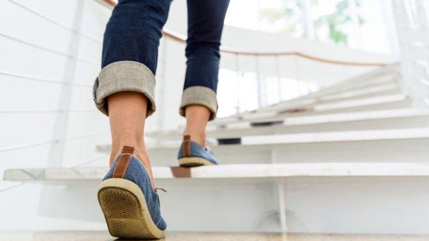 Una mujer subiendo las escaleras