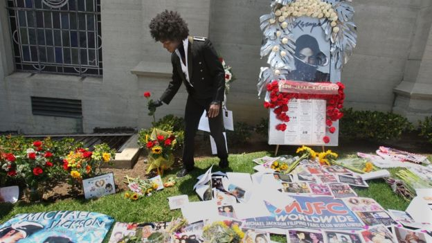 A man adjusts a flower at a memorial to Michael Jackson