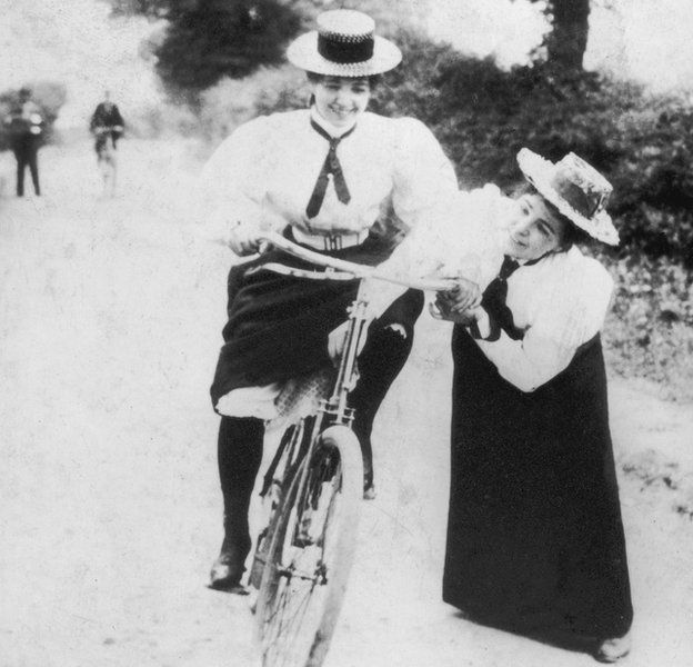 A young woman bicyclist is helped by a friend as she tries to maintain her balance, 1885