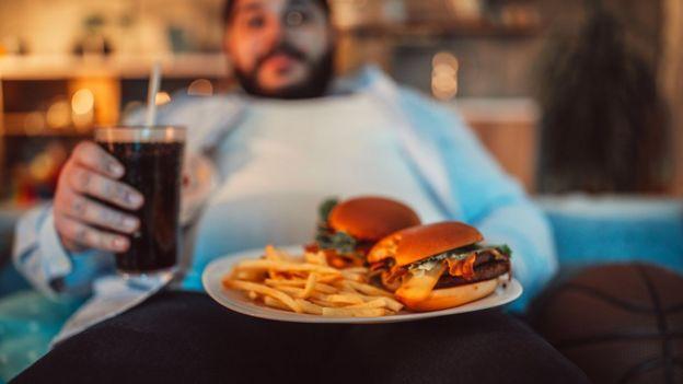 Homem sentado em um sofá degustando uma comida rica em gorduras.