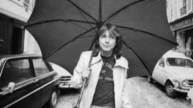 David Cassidy walking down a road in London with an umbrella (30 April 1974)