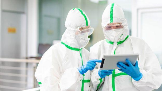 Dos médicos protegidos analizan resultados en una tableta.