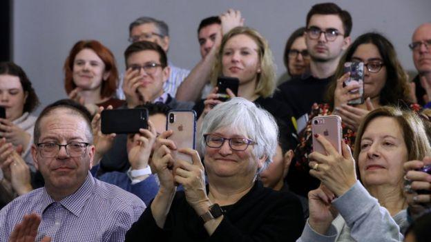 Un grupo de personas asisten a un acto de campaña de la senadora Elizabeth Warren.