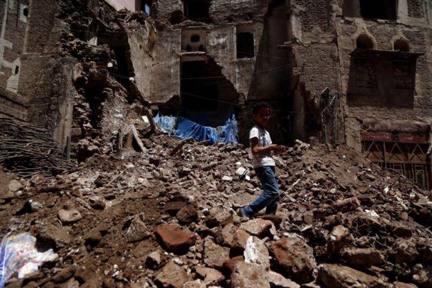 طفل يمشي على أنقاض مبنى تاريخي بعد أن انهار جزئيا بسبب الأمطار الغزيرة في مدينة صنعاء القديمة، 13 أغسطس/آب 2020