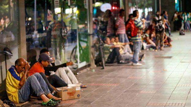 Venezolanos sentados en el suelo