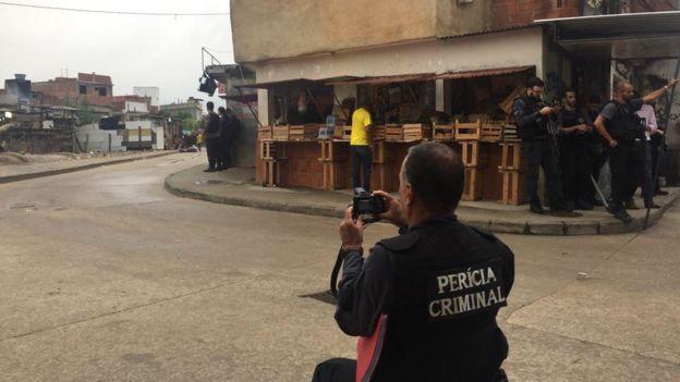 Peritos na rua São Daniel fotografando a torre branca ao fundo da favela