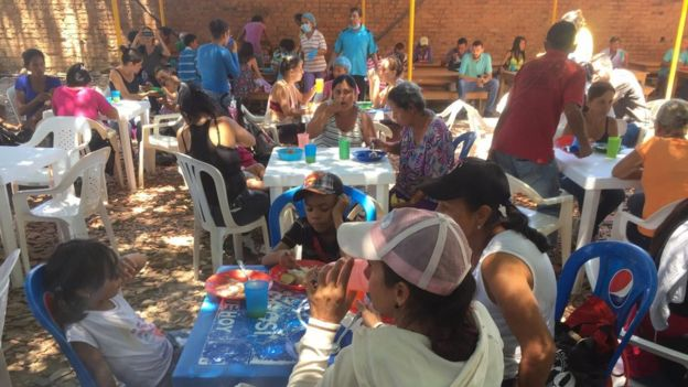 People sit at plastic tables and eat in the courtyard of a church in Cúcuta